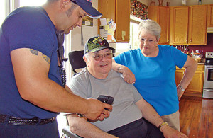 Lt. Brian Olivas shows Fred and Ginger Stevenson photos of the progress on the Help for Homes project to improve accessibility and safety in their home.