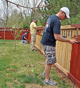 From left, Chief Mark Bodane, Firefighter Richard Towndrow and Lt. Sean McCulloch stain the fence that was power washed a couple of days earlier.