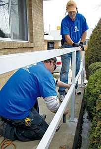Brothers construction technicians install a porch railing as part of improvements for a metro-area senior.