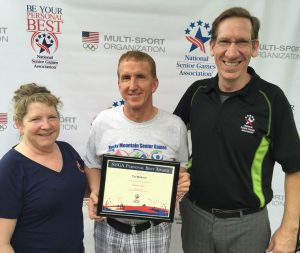 Senior athlete Tom McAdam (center) is congratulated for a national Personal Best Award by NSGA CEO Marc T. Riker (right) and Rocky Mountain Senior Games President (and current NSGA Board Vice Chair) Kate Amack.