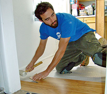 A Brothers Redevelopment construction technician replaces a worn kitchen floor that had become a tripping hazard with new flooring.